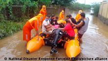 22.07.21 *** This photograph provided by India's National Disaster Response Force (NDRF) shows NDRF personnel rescuing people stranded in floodwaters in Bhiwandi, in the western Indian state of Maharashtra, Thursday, July 22, 2021. Landslides triggered by heavy monsoon rains hit parts of western India, killing at least five people and leading to the overnight rescue of more than 1,000 other people trapped by floodwaters, an official said Friday. (National Disaster Response Force via AP)