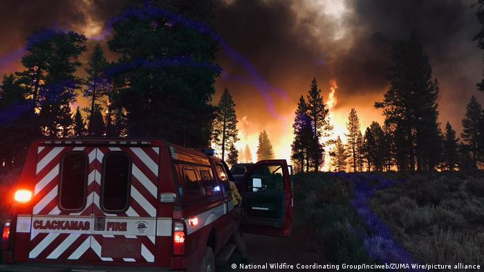 The Bootleg fire burns in southeast Oregon, at night, with a fire truck in the foreground