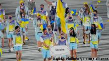 Olena Kostevych and Bogdan Nikishin, of Ukraine, carry their country's flag during the opening ceremony in the Olympic Stadium at the 2020 Summer Olympics, Friday, July 23, 2021, in Tokyo, Japan. (AP Photo/David J. Phillip)