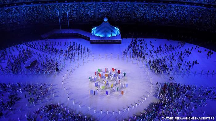 Fuera del círculo, los cerca de 11.000 titulares olímpicos que participaron en la ceremonia inaugural.