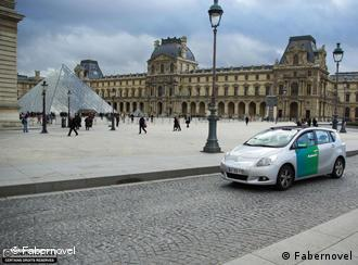 An electric car is shown, parked outside of the Louvre