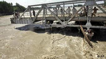 People stand on the remains of a broken bridge in Nowshera