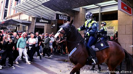 Anti-lockdown protesters face of against police on horseback in Sydney