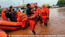 This photograph provided by India's National Disaster Response Force (NDRF) shows NDRF personnel rescuing residents in Chiplun area in the western Indian state of Maharashtra, Friday, July 23, 2021. Officials say landslides and flooding triggered by heavy monsoon rain have killed more than 100 people in western India. More than 1,000 people trapped by floodwaters have been rescued.(National Disaster Response Force via AP)
