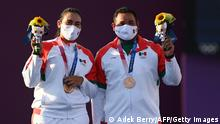 (L-R) Bronze medallists Mexico's Alejandra Valencia and Luis Alvarez stand on the podium during the mixed team victory ceremony during the Tokyo 2020 Olympic Games at Yumenoshima Park Archery Field in Tokyo on July 24, 2021. (Photo by ADEK BERRY / AFP) (Photo by ADEK BERRY/AFP via Getty Images)