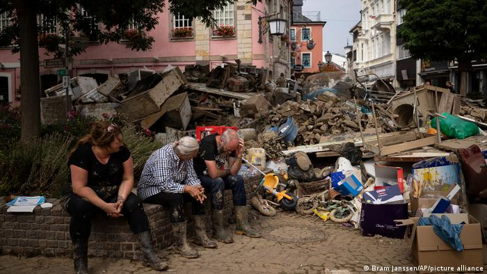 People rest from cleaning up the debris of the flood disaster in Bad Neuenahr-Ahrweiler