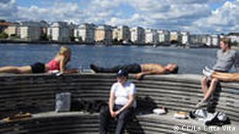 People sun themselves at the pier in the Swedish town of Hammarby
