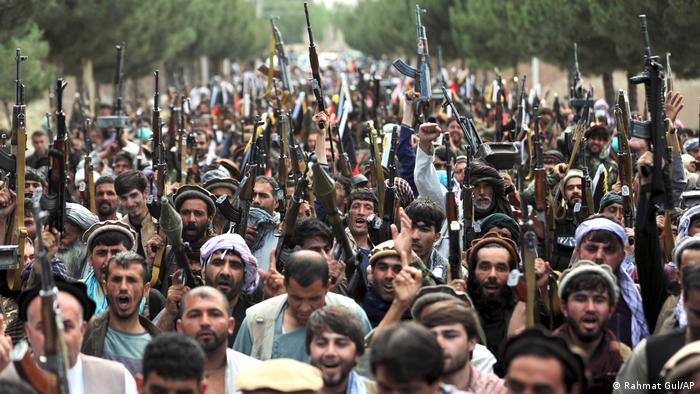 Afghan militiamen join Afghan defense and security forces in mobilizing in the streets with weapons including rifles and RPGs pointed towards the sky