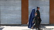 A family walks at a market in Kabul on July 22, 2021. (Photo by SAJJAD HUSSAIN / AFP)