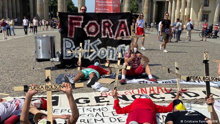 Foto mostra pessoas deitadas sobre os cartazes e segurando cruzes de madeira. Ao fundo uma pessoa segura um cartaz com o dizer: Fora Bolsonaro.
