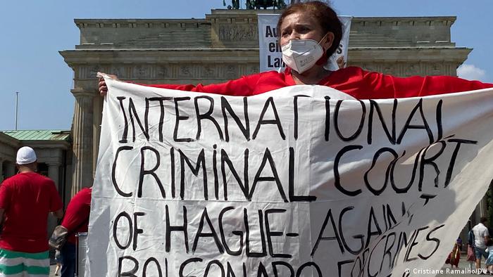 Mulher de roupa vermelha e máscara segura uma faixa onde se lê: Internacional Criminal Court of Hague Against Bolsonaro Crimes.