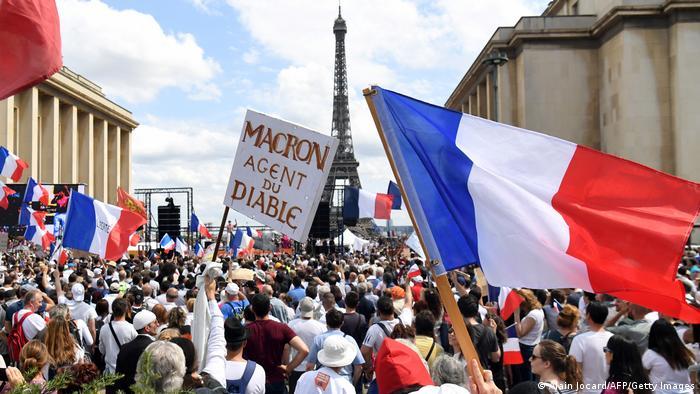 Foto mostra muitas pessoas, com a torre Eifel ao fundo. Algumas portam bandeiras da França.