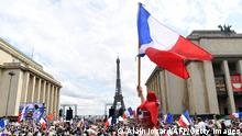 A protester wearing a Phrygian cap to resemble Marianne, the embodiment of the French Republic, waves a national flag during a protest against the compulsory vaccination for certain workers and the mandatory use of the health pass called by the French government, on the Droits de l'homme (human rights) esplanade at the Trocadero Square, in front of the Eiffel Tower in Paris on July 24, 2021. - Since July 21, people wanting to go to in most public spaces in France have to show a proof of Covid-19 vaccination or a negative test, as the country braces for a feared spike in cases from the highly transmissible Covid-19 Delta variant. (Photo by Alain JOCARD / AFP) (Photo by ALAIN JOCARD/AFP via Getty Images)