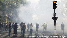 Protesters, some wearing yellow vests, stands amidst tear gas smoke during a demonstration against the compulsory vaccination for certain workers and the mandatory use of the health pass called by the French government in Paris on July 24, 2021. - Since July 21, people wanting to go to in most public spaces in France have to show a proof of Covid-19 vaccination or a negative test, as the country braces for a feared spike in cases from the highly transmissible Covid-19 Delta variant. (Photo by Sameer Al-DOUMY / AFP) (Photo by SAMEER AL-DOUMY/AFP via Getty Images)