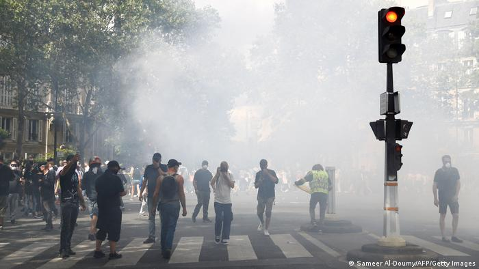 Protesters stand amidst tear gas smoke during a demonstration against compulsory vaccination for certain workers
