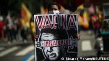 A protestor holds a banner in which reads Vaccine and Impeachment during a demonstration against the Brazil's President Jair Bolsonaro's handling of the coronavirus disease (COVID-19) pandemic and demanding his impeachment, in Rio de Janeiro, Brazil, July 24, 2021. REUTERS/Ricardo Moraes