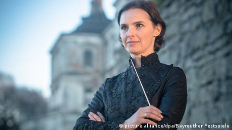 Oksana Lyniv mit Dirigentenstab vor vor einer Mauer