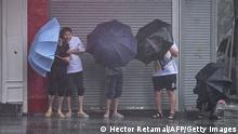 People seek shelter from the rain and wind along a street in Ningbo on July 25, 2021, as Typhoon In-Fa lashes the eastern coast of China. (Photo by Hector RETAMAL / AFP) (Photo by HECTOR RETAMAL/AFP via Getty Images)