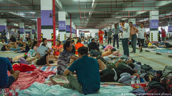 Construction workers take emergency shelter in a parking lot in Ningbo, Zhejiang Province, China