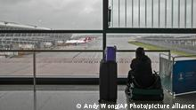 25.07.2021 A passenger sits on her luggage watching passenger airplanes parked on the tarmac after all flights were canceled at Pudong International Airport in Shanghai, China, Sunday, July 25, 2021. Airline flights were canceled in eastern China and cargo ships were ordered out of the area Saturday as Typhoon In-fa churned toward the mainland after dumping rain on Taiwan. (AP Photo/Andy Wong)
