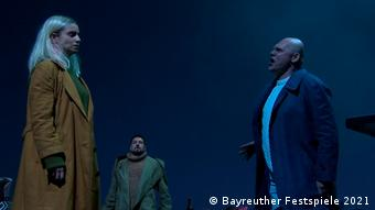 A blonde woman in an ochre coat listens to a man in a dark coat. In the background is another man in a green coat