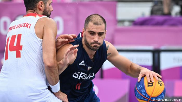 Poland's Pawel Pawlowski fights for the ball with Serbia's Dusan Domovic Bulut during the men's first round 3x3 basketball match between Poland and Serbia at Tokyo 2020