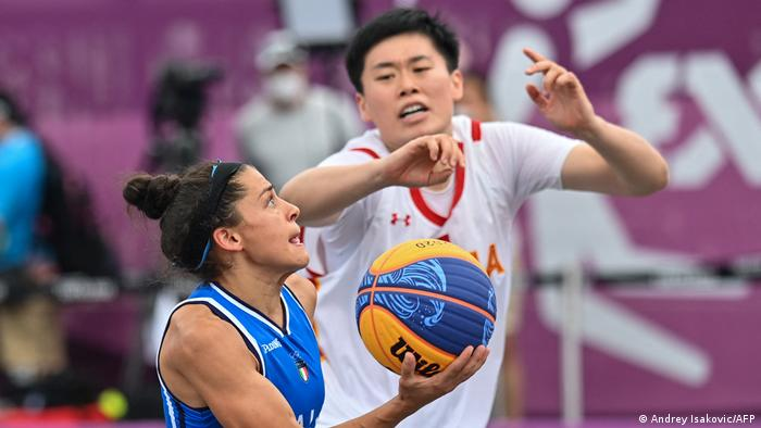Italy's Raelin Alie fights for the ball with China's Zhang Zhiting during the women's first round 3x3 basketball match between China and Italy