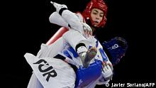 Turkey's Hatice Kubra Ilgun (Blue) and Refugee Olympic Team's Kimia Alizadeh Zenoorin (Red) compete in the taekwondo women's -57kg bronze medal B bout during the Tokyo 2020 Olympic Games at the Makuhari Messe Hall in Tokyo on July 25, 2021. (Photo by Javier SORIANO / AFP)