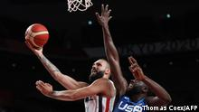 France's Evan Fournier (L) goes to the basket as USA's Draymond Jamal Green tries to block in the men's preliminary round group A basketball match between France and USA during the Tokyo 2020 Olympic Games at the Saitama Super Arena in Saitama on July 25, 2021. (Photo by Thomas COEX / AFP)