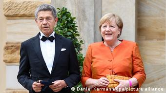 Angela Merkel in an orange top, and her husband Joachim Sauer in a tuxedo, smile for the camera
