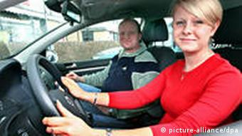 A young woman takes a practical driving lesson