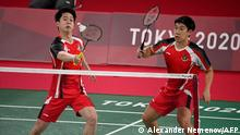 Indonesia's Kevin Sanjaya Sukamuljo (L) hits a shot next to partner Indonesia's Marcus Fernaldi Gideon in their men's singles badminton group stage match against Britain's Sean Vendy and Britain's Ben Lane during the Tokyo 2020 Olympic Games at the Musashino Forest Sports Plaza in Tokyo on July 24, 2021. (Photo by Alexander NEMENOV / AFP)