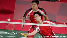 Indonesia's Kevin Sanjaya Sukamuljo (front) hits a shot next to partner Indonesia's Marcus Fernaldi Gideon in their men's doubles badminton group stage match against Britain's Sean Vendy and Britain's Ben Lane during the Tokyo 2020 Olympic Games at the Musashino Forest Sports Plaza in Tokyo on July 24, 2021. (Photo by Alexander NEMENOV / AFP)
