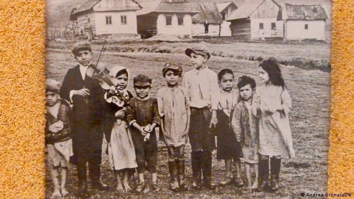 Ein Schwarz-Weiß-Foto vor orangenem Hintergrund: Es zeigt eine Gruppe von neun Mädchen und Jungen nebeneinander. Der 2. von links, ein größerer Junge spielt auf einer Geige. Im Hintergrund sind mehrere Häuser eines Dorfes zu erkennen