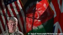 Генерал Кеннет Маккензи выступает в Кабуле на фоне флагов США, Афганистана и Великобритании