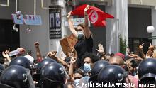 TOPSHOT - A Tunisian protester lifts a national flag at an anti-government rally as security forces block off the road in front of the Parliament in the capital Tunis on July 25, 2021. (Photo by FETHI BELAID / AFP) (Photo by FETHI BELAID/AFP via Getty Images)