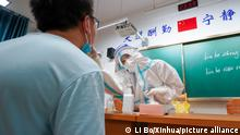 25.07.2021 (210725) -- NANJING, July 25, 2021 (Xinhua) -- Wang Yu (R) takes a swab sample from a resident for COVID-19 test at a testing site of Longxi Community in Jiangning District of Nanjing, capital of east China's Jiangsu Province, July 25, 2021. A second round of COVID-19 nucleic acid test was launched Saturday night in Jiangning District of Nanjing. Wang Yu, a nurse from Dongshan Community Hospital in Jiangning District, was racing against time in epidemic battle on Saturday night. Wang, along with other medical workers and community workers, has been busy conducting nucleic acid tests for the residents until late night. (Xinhua/Li Bo)