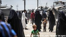 23.06.2021 People walk about at the Kurdish-run al-Hol camp, which holds relatives of suspected Islamic State (IS) group fighters, in Hasakeh governorate in northeastern Syria, on June 23, 2021. (Photo by Delil SOULEIMAN / AFP) (Photo by DELIL SOULEIMAN/AFP via Getty Images)
