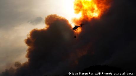 Ein Löschhubschrauber fliegt durch den Rauch