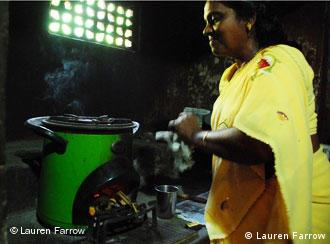 A woman cooks on a new less polluting stove marketed by Envirofit