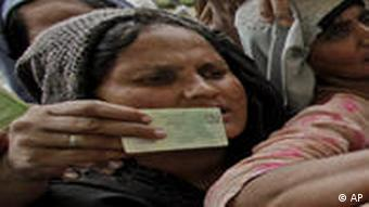 Women show their ID cards to access relief supplies