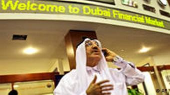 A man holds a phone beneath a sign at the Dubai Financial Market