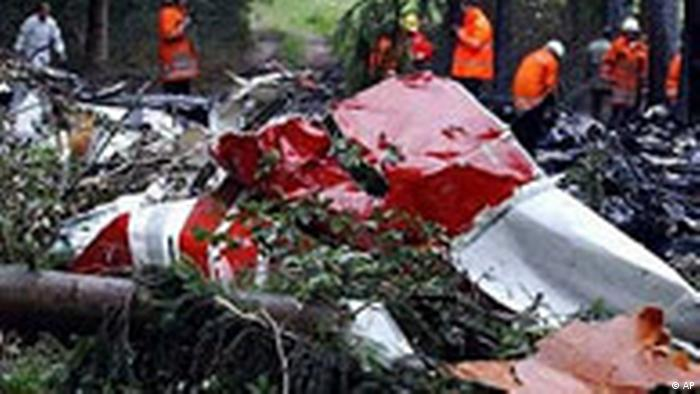 Homens inspecionam destroços de um avião. É possível ver restos da fuselagem vermelha