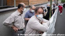 19.07.2021 An Iranian man wearing a protective face mask looks on as people line-up out of a sport hall while waiting to receive a dose of the China's Sinopharm new coronavirus disease (COVID-19) vaccine in central Tehran on July 19, 2021. (Photo by Morteza Nikoubazl/NurPhoto)