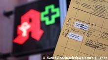 27.06.2021, Mitte, Berlin, Vor dem Logo einer Apotheke befindet sich ein Impfausweis mit zwei Impfeintragungen gegen Covid 19.