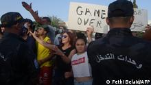 Eine Frau hält ein Schild hoch auf dem Game over bei Protesten in Tunis