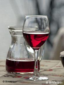 A wine glass sits next to a carafe