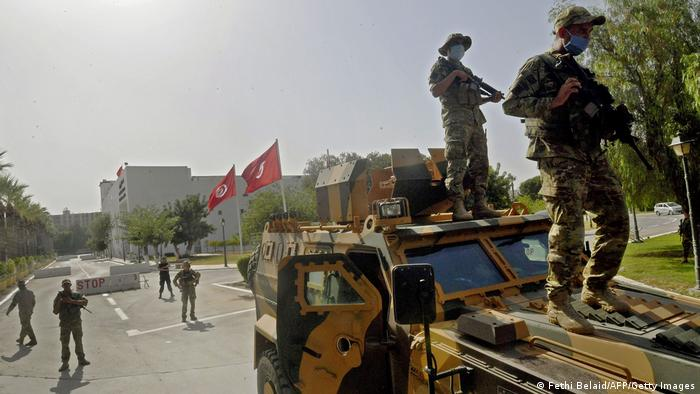 Soldiers on the ground and two on a military vehicle, flags and a building in the background