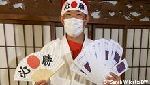 Homem japonês de cabelos vermelhos, usando máscara facial, quimono branco de judô e faixa com letras japonesas na cabeça, portando um leque e bilhetes de ingressos