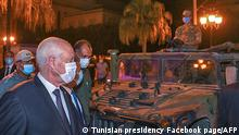 26.7.2021***A handout picture provided by the Tunisian Presidency Facebook Page on July 26, 2021 shows Tunisian President Kais Saied walking past a military vehicle as he walks in Tunis's central Habib Bourguiba Avenue, after he ousted the prime minister and ordered parliament closed for 30 days. - Tunisia was plunged deeper into crisis as Saied suspended parliament and dismissed Prime Minister Hichem Mechichi late July 25, prompting the country's biggest political party to decry a coup d'etat (Photo by - / Tunisian presidency Facebook page / AFP) / === RESTRICTED TO EDITORIAL USE - MANDATORY CREDIT AFP PHOTO / HO / PRESIDENCY FACEBOOK PAGE - NO MARKETING NO ADVERTISING CAMPAIGNS - DISTRIBUTED AS A SERVICE TO CLIENTS ===